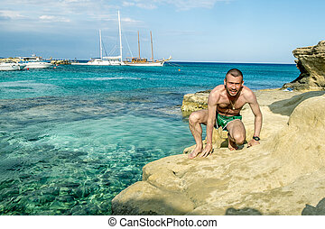 A man in shorts posing on the beautiful beach of...