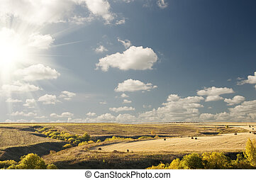 Big sun cloudy blue sky above an autumn landscape - Big...