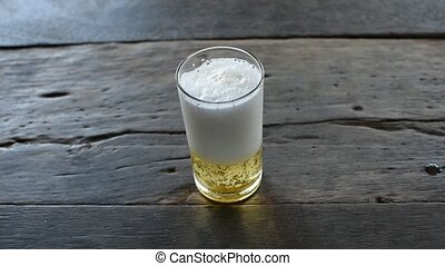 Beer with ice in glass - Beer in glass with ice and froth on...