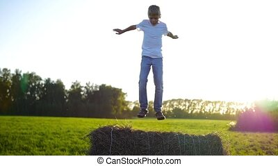 child have fun jumping on the hay