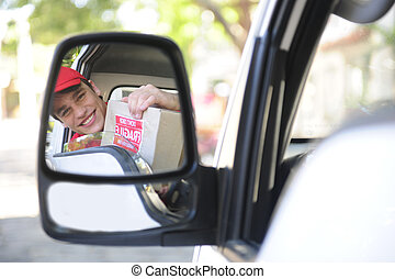 delivery courier in van, rear view mirror - happy postal...