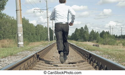 Businessman runs along the rails from camera