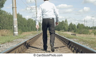 Businessman walks along the rails from camera