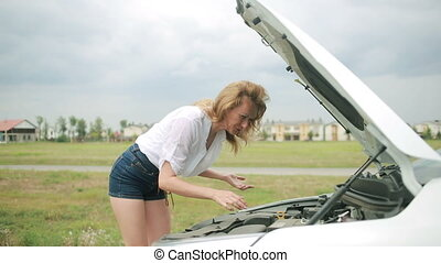 woman opens the hood Broken car girl looks at a damaged...