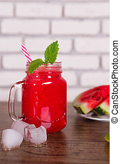 Blended red fruit smoothie in glass jar with straw, ice pieces. Watermelon slices on plate. Selective focus. Harvest Concept.