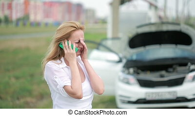 woman and broken car calling for help on cell phone. woman...