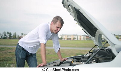 Man looking at engine of car. man repairing broken car - Man...