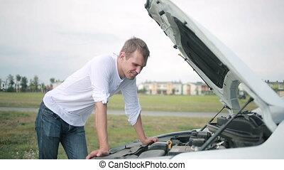 Man looking at engine of car. man repairing broken car