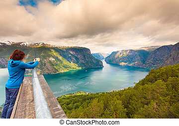 Tourist taking photo from Stegastein viewpoint Norway -...