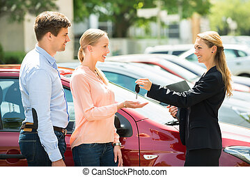 Dealer Giving Car Key To Couple - Side View Of Female Dealer...