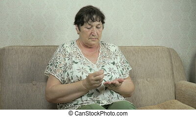 Old woman considers pills on her palm