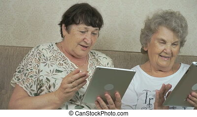 Old women holding the silver digital tablets - Old women...