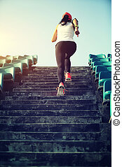 young fitness woman runner athlete running up on stairs