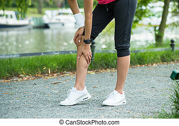 Female Jogger Having Pain In Her Knee - Close-up Of Female...