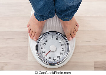 Person Standing On Weighing Scale - Low Section Of A Person...