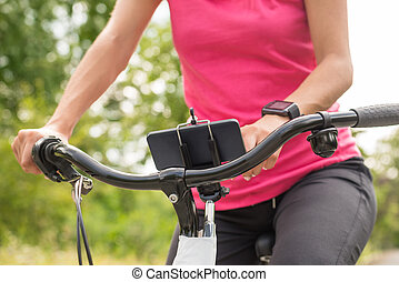 Female Cyclist Touching At Smart Phone On Bicycle - Close-up...