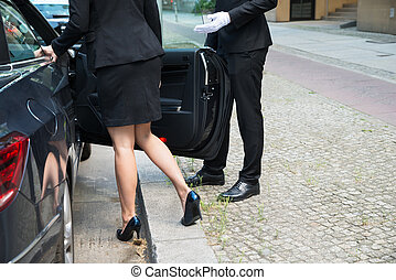 Male Chauffeur Opening The Car Door For The Businesswoman On...