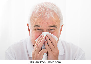 Man Infected With Cold Blowing His Nose - Close-up Of Senior...