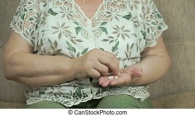 Elderly woman considers tablets on her palm