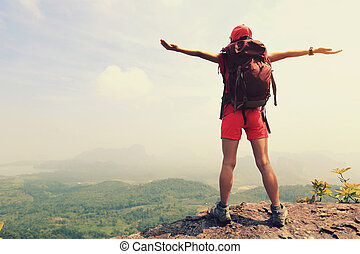 cheering successful woman backpacker open arms on mountain...