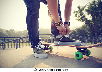 skateboarder tying shoelace at skatepark ramp