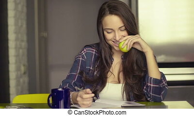 Smiling beautiful young woman sitting writing in her dining...