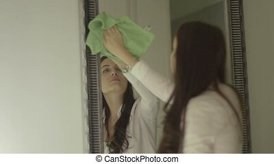 Smiling brunette woman cleaning mirror at home, view from...