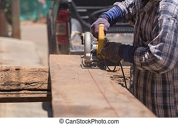 carpenter use electric saw to sawing wood board