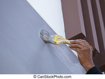 Hand holding brush painting wall with gray colorl