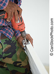 door installation. Worker drills a hole for bolt of hinge -...