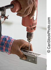 door installation Worker drills a hole for bolt of hinge -...