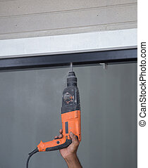 worker drilling holes in aluminium construction frame with...