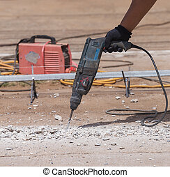 Worker repairing and drilling concrete road - Worker...
