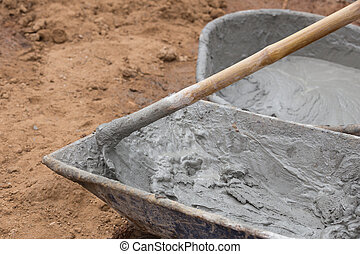 Cement blending by hoe in a tray at construction site