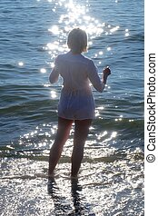 Woman silhouette on beach with glittering water. - Sunset...