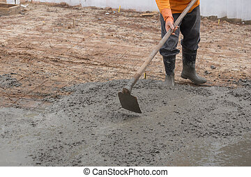 worker use hoe on a newly poured concrete floor at...