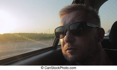 Young casual man with beard portrait sitting on the backseat...