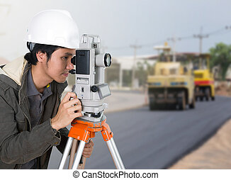 engineer working with survey equipment theodolite with road...