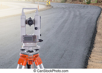Survey equipment theodolite on a tripod with road under...
