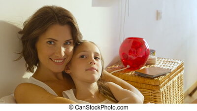 Beautiful mother hugs her cute daughter and smile, at home...