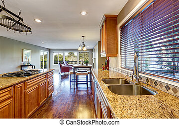 Open floor plan. Kitchen room interior with island and granite counter top.