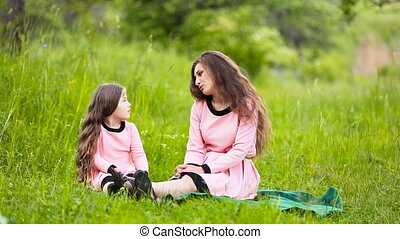 Mom and daughter in nature - mother and daughter sit on...