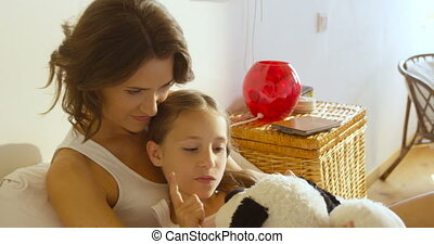 Family relationships. Mother hugging her daughter holding soft toy. The concept of care and reliability