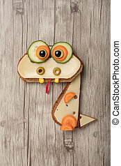 Funny dragon made of bread and cheese on wooden background