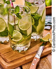 On wooden boards is glasses with mohito and knife - Alcohol...