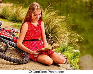 Girl read book near bicycle on river beach - Girl wearing...