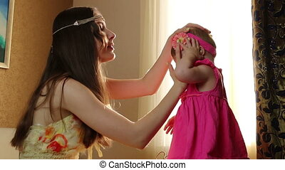 Mom puts little daughter rim on the hair. small child playing with his mother in the room on a bed
