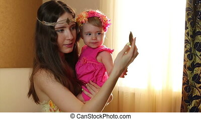 mother with her daughter plays with a mirror. - Close up of...