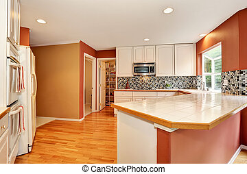White kitchen room interior with tile counter top and hardwood floor.