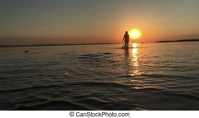 The girl runs on the water at sunset